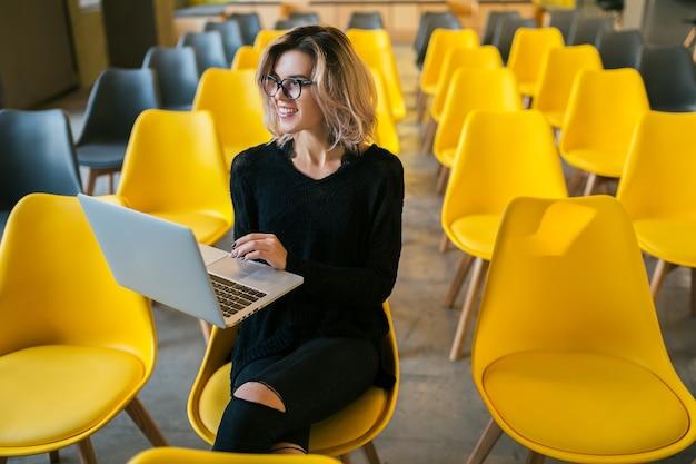 Ritratto di giovane donna attraente seduto in aula lavorando sul laptop con gli occhiali, apprendimento degli studenti in aula con molte sedie gialle