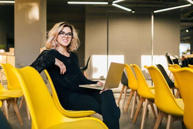 Portrait of young attractive woman sitting in lecture hall working on laptop wearing glasses, student learning in classroom with many yellow chairs
