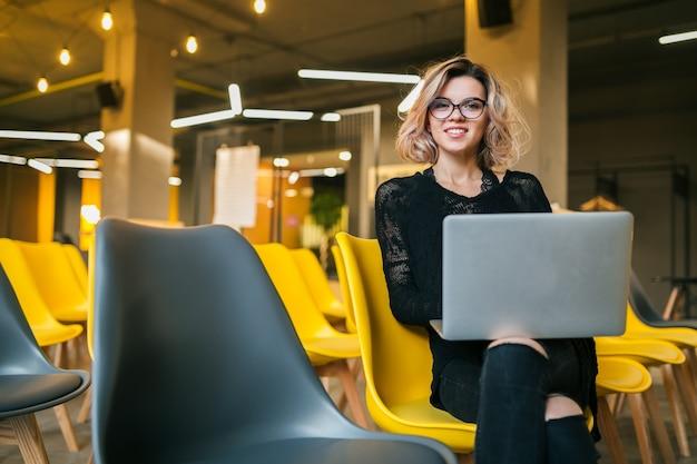 Ritratto di giovane donna attraente che si siede nell'aula di conferenza che lavora agli occhiali da portare del computer portatile, studente che impara nell'aula con molte sedie gialle