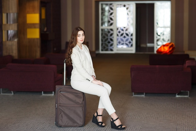 Portrait young attractive woman sitting on suitcases in the terminal or train station. the girl met on a trip.