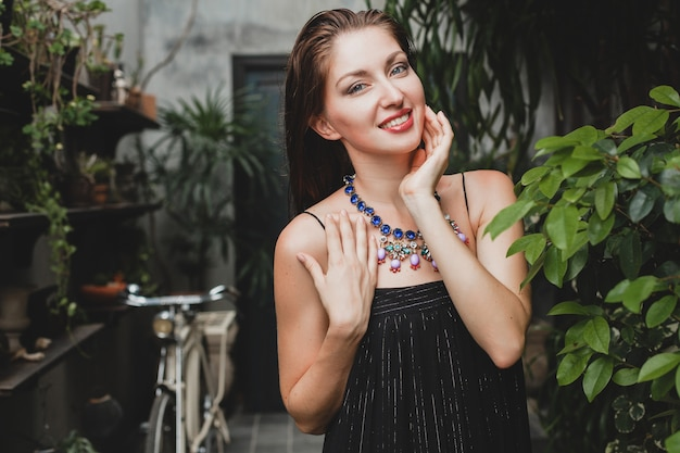 Portrait of young attractive woman in stylish black dress posing at tropical villa, sexy, elegant summer style, fashionable necklace accessories, smiling, jewelry, pure natural skin of face