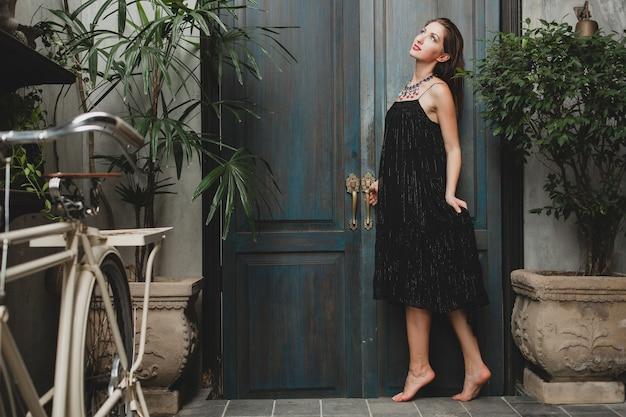 Ritratto di giovane donna attraente in vestito nero alla moda che propone alla villa tropicale, stile estivo sexy ed elegante, accessori per collana alla moda, sorridente, umore romantico, lusso