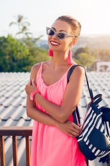 Ritratto di giovane donna attraente in elegante abito rosa estivo, indossando occhiali da sole e zaino, sorridente, felice, tendenza della moda, elegante stile casual moderno per i giovani