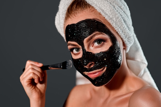 Portrait of a young attractive woman with a towel on her head applying a black cleansing mask with a brush to her face on a gray wall.