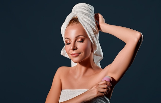 Portrait of a young attractive woman with a towel on her head uses a ball antiperspirant on a black wall