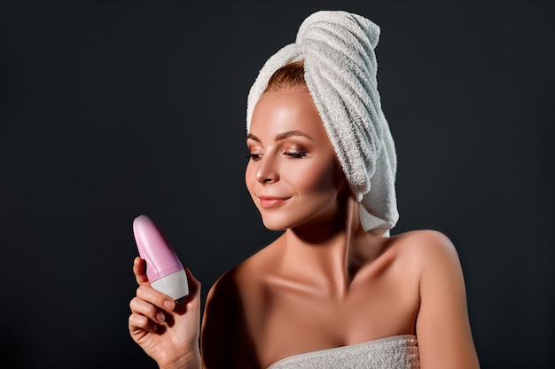 Portrait of a young attractive woman with a towel on her head uses a ball antiperspirant on a black wall.