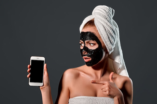 Portrait of a young attractive woman with a towel on her head with a black cleansing mask on her face with a phone on a gray wall.