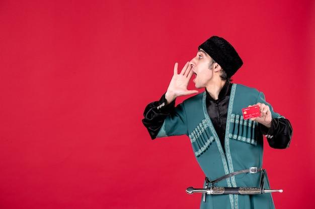 Ritratto di giovane uomo azero in costume tradizionale con carta di credito su red