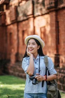 Portrait young backpacker female wearing hat traveling in ancient site, she use camera to taking photo with happiness, copy space