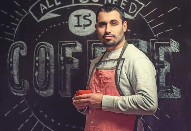 Portrait of a young baristas in a red apron with a cup in the hands of a small coffee shop.