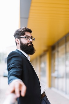 Portrait of young beard businessman with black eyeglasses looking away