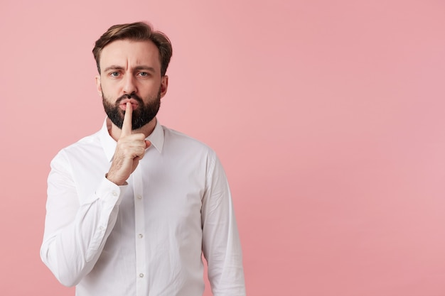 Portrait of young bearded brunette man with short haircut raising hand with hush gesture, looking to front with serious face and frowning eyebrows, standing over pink wall in formal clothes
