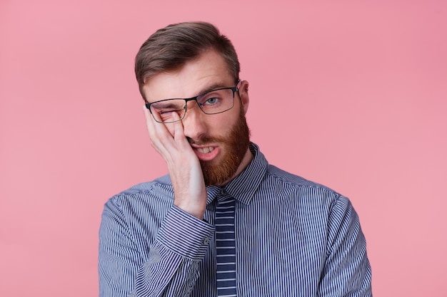 Portrait of young bearded businessman wears glasses feels unhappy and tired, propping up his head, isolated over pink background.