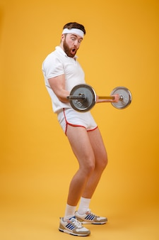 Portrait of a young bearded fitnes man doing workout