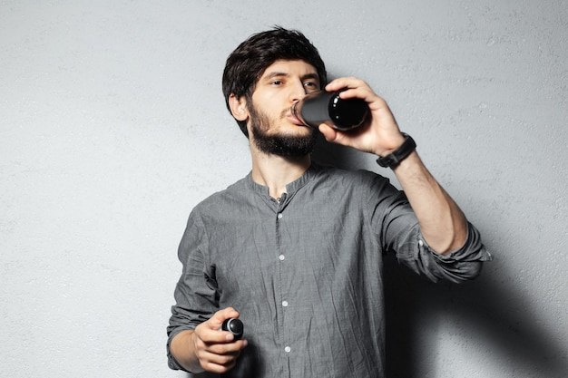 Portrait of young bearded guy, drinking water from black stainless bottle, on textured of grey.