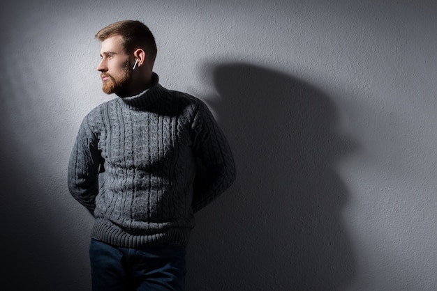 Portrait of a young bearded guy of twenty-five years old. in a warm winter sweater, proudly, gray, looks away.