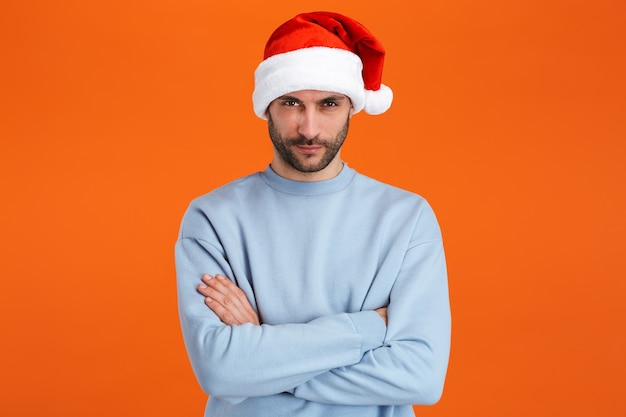 Portrait of young bearded handsome man wearing santa claus red hat looking at camera isolated over orange wall