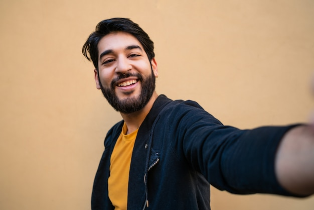 Portrait of young bearded hipster man looking at camera and taking a selfie against yellow.