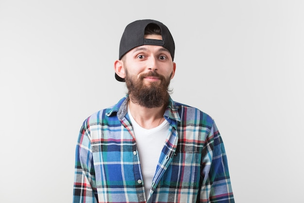 Portrait of a young bearded hipster stylish guy over white wall.