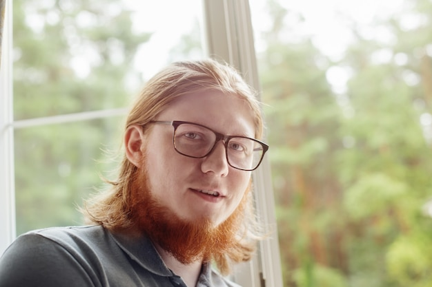 Portrait of  young bearded man against  background of  window