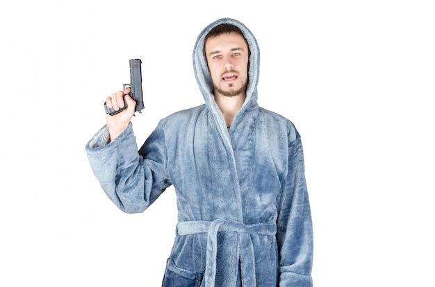 Portrait of young bearded man in blue bathrobe with black firearm