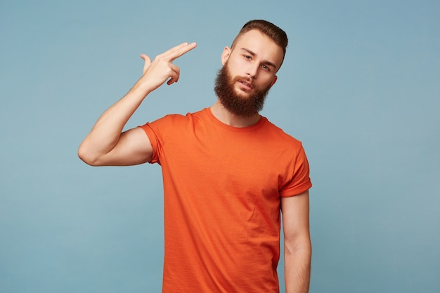 Portrait of young bearded man committing suicide with finger gun gesture. portrait of despaired guy shooting himself making finger pistol sign against blue wall. human face expressions