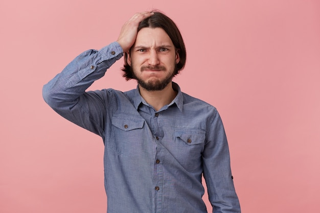 Portrait of young bearded man in denim shirt, hold his head, blowing cheeks and bites lips, forgot something important, made a mistake. isolated over oink background.
