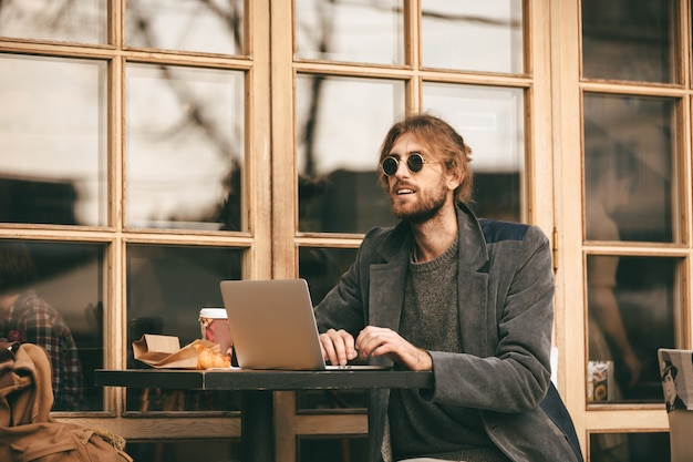 Portrait of a young bearded man in earphones sitting
