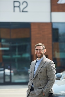 Portrait of young bearded man in eyeglasses smiling at camera while standing in the city