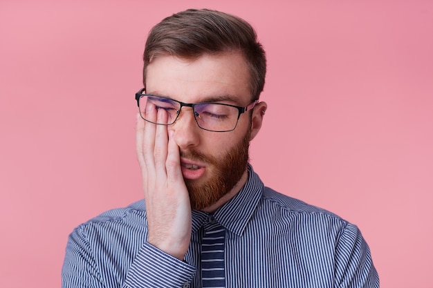 Portrait of young bearded man in glasses, tired of working and falling asleep, propping up his head, isolated over pink background.