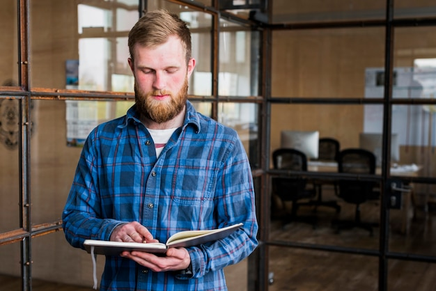 Portrait of young bearded man reading diary in office