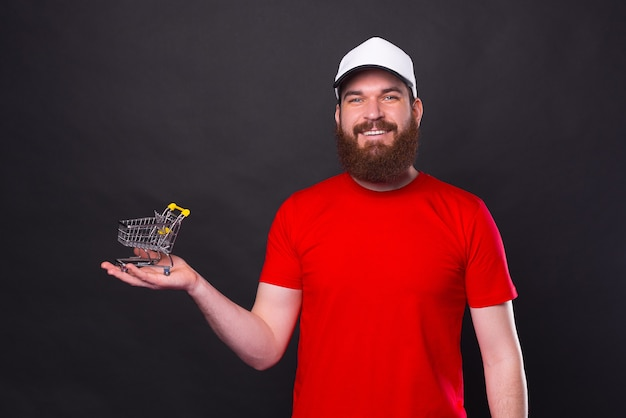 Portrait of young bearded man in red t-shirt holding small shopping trolley over black