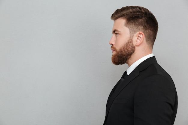 Ritratto di un giovane uomo barbuto in tuta guardando avanti
