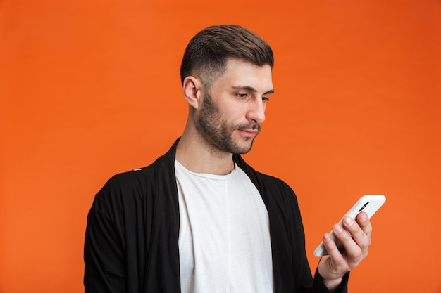 Portrait of young bearded man wearing basic clothes holding cellphone isolated over orange wall