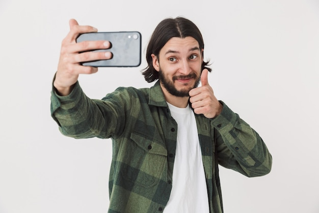 Portrait of a young bearded man wearing casual clothes standing isolated over wall, taking a selfie, thumbs up