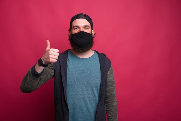 Portrait of a young bearded man wearing protective mask