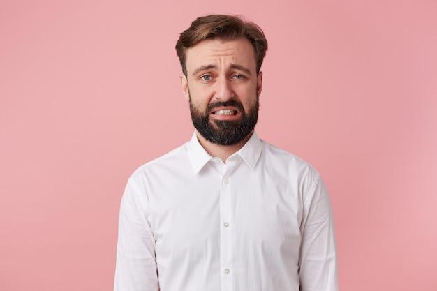 蜘蛛を見た肖像画の若いひげを生やした男。ピンクの背景の上に孤立した嫌悪感で見えます。