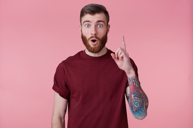 Ritratto di giovane uomo barbuto con la mano tatuata, ha trovato una soluzione al problema, mostrando il dito indice verso l'alto ha l'idea, pensiero ispirazione isolata su sfondo rosa.