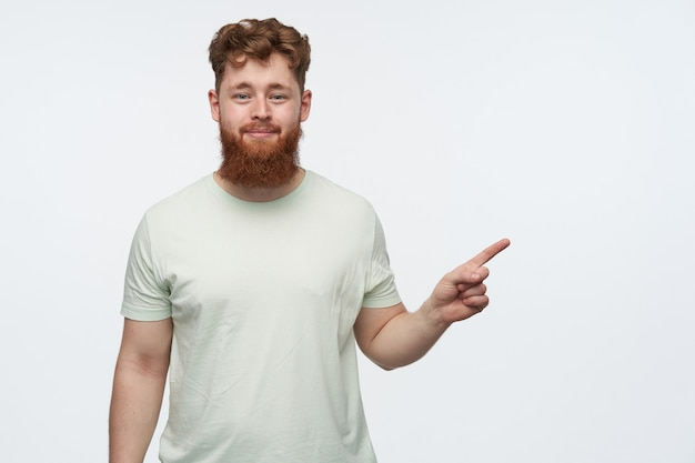 Portrait of young bearded redhead guy, wears blank t-shirt, pointing with a finger at right side copy space
