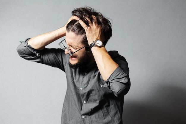 Portrait of young bearded screaming guy with disheveled hair and glasses