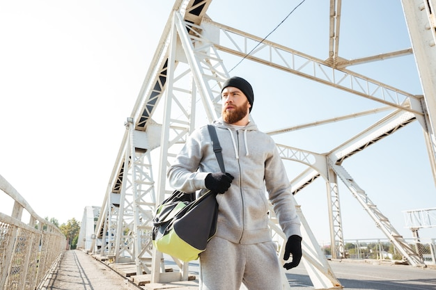Portrait of a young bearded sports man with bag walking along urban bridge