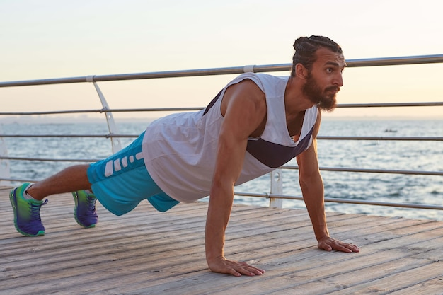 Portrait of young bearded sporty gay doing pushups, keeps the plank, doing morning exercises by the sea, warm-up after run, leads healthy active lifestyle. fitness and healthy concept.