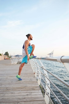 Portrait of young bearded sporty guy doing morning exercises by the sea, stretching for legs, warm-up after running.