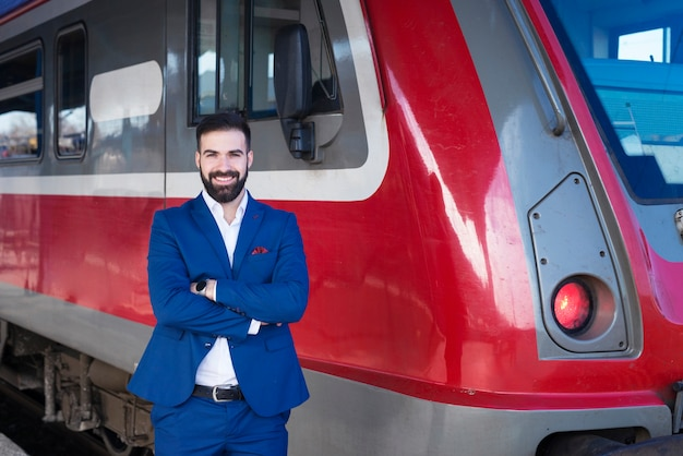 Portrait of young bearded train driver in blue uniform proudly standing in front of modern subway train