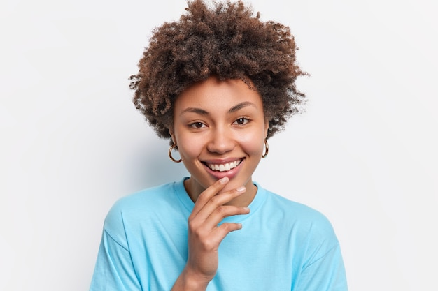 Portrait of young beautiful african american keeps hand on chin smiles gently looks directly  dressed in blue t shirt expresses positive emotions isolated over white  wall