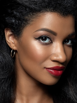 Portrait of young beautiful african woman with evening make up