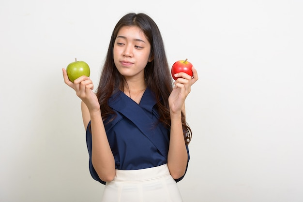 Portrait of young beautiful asian businesswoman choosing between two apples