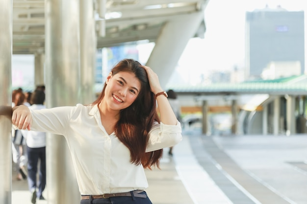 Portrait of young beautiful asian businesswoman touch her hairs at modern footbridge.