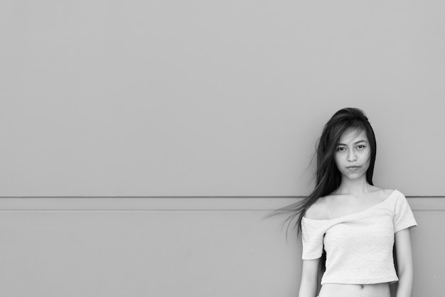 Portrait of young beautiful asian girl on concrete wall outdoors in black and white