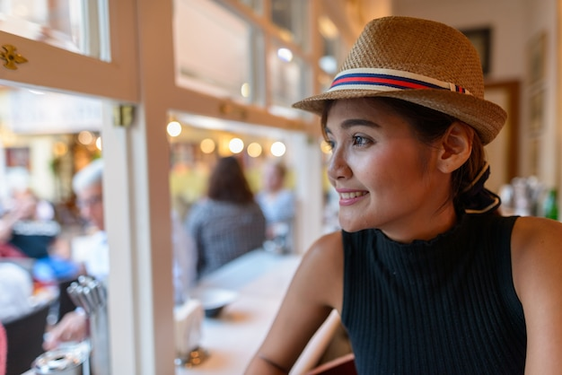 Portrait of young beautiful asian tourist woman sitting inside the restaurant in spain